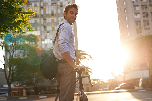 Young man on his way to his creative job on his bike